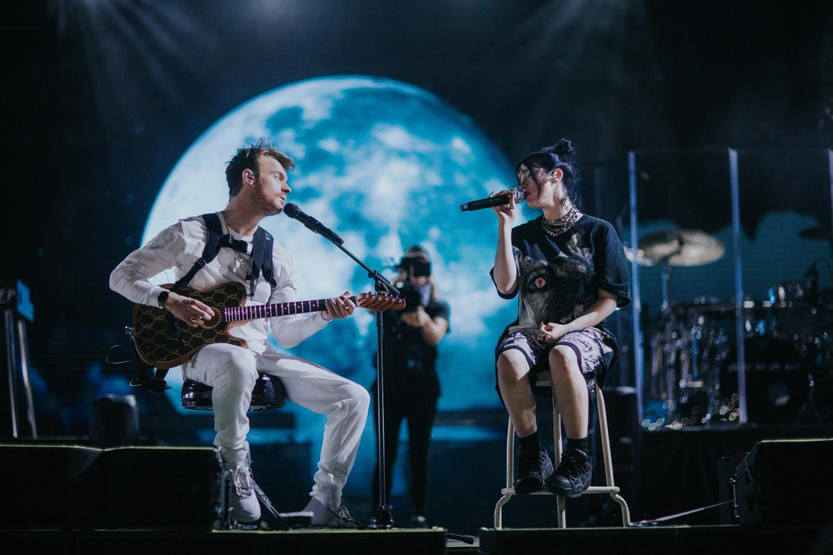 """Billie Eilish and Finneas O'Connell on stage in """"Billie Eilish: The World's A Little Blurry."""" Cr: Apple TV+"""
