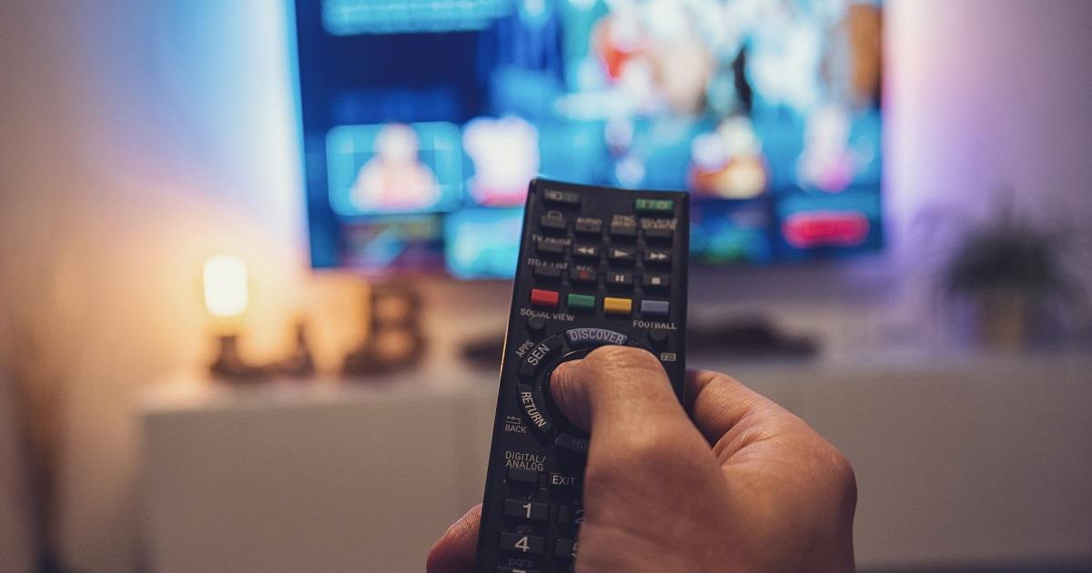 Hand holding remote control aimed at a television screen.