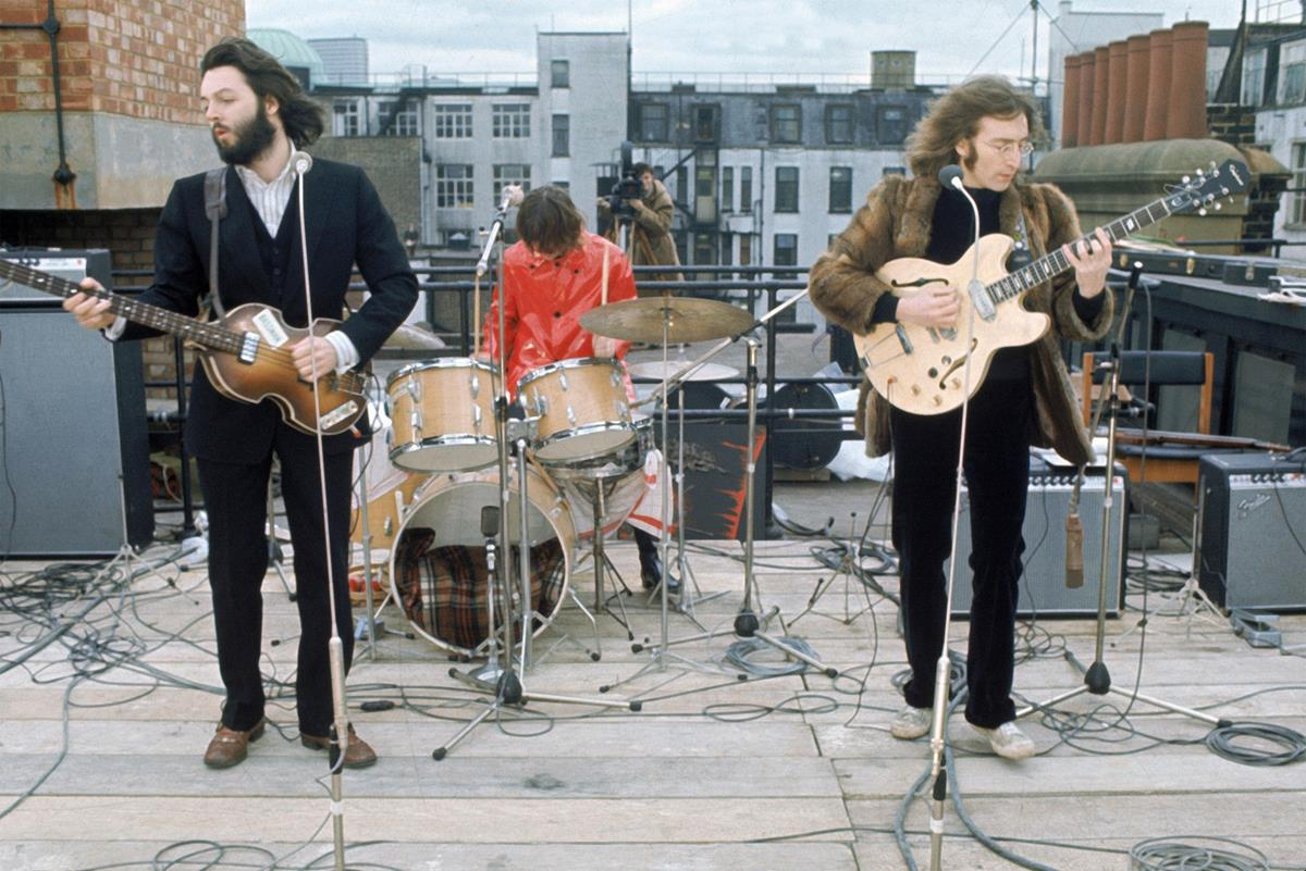 """The Beatles perform their final concert on the roof of Apple headquarters. """"The Beatles: Get Back."""" Cr: Apple Corps Ltd./Disney"""
