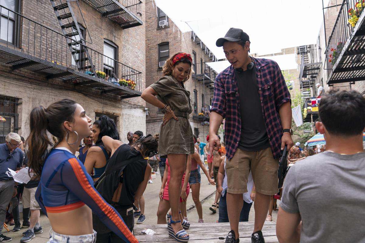 "Melissa Barrera, Daphne Rubin-Vega and director Jon M. Chu on the set of the screen adaptation of ""In The Heights."" Cr: Macall Polay/Warner Bros."