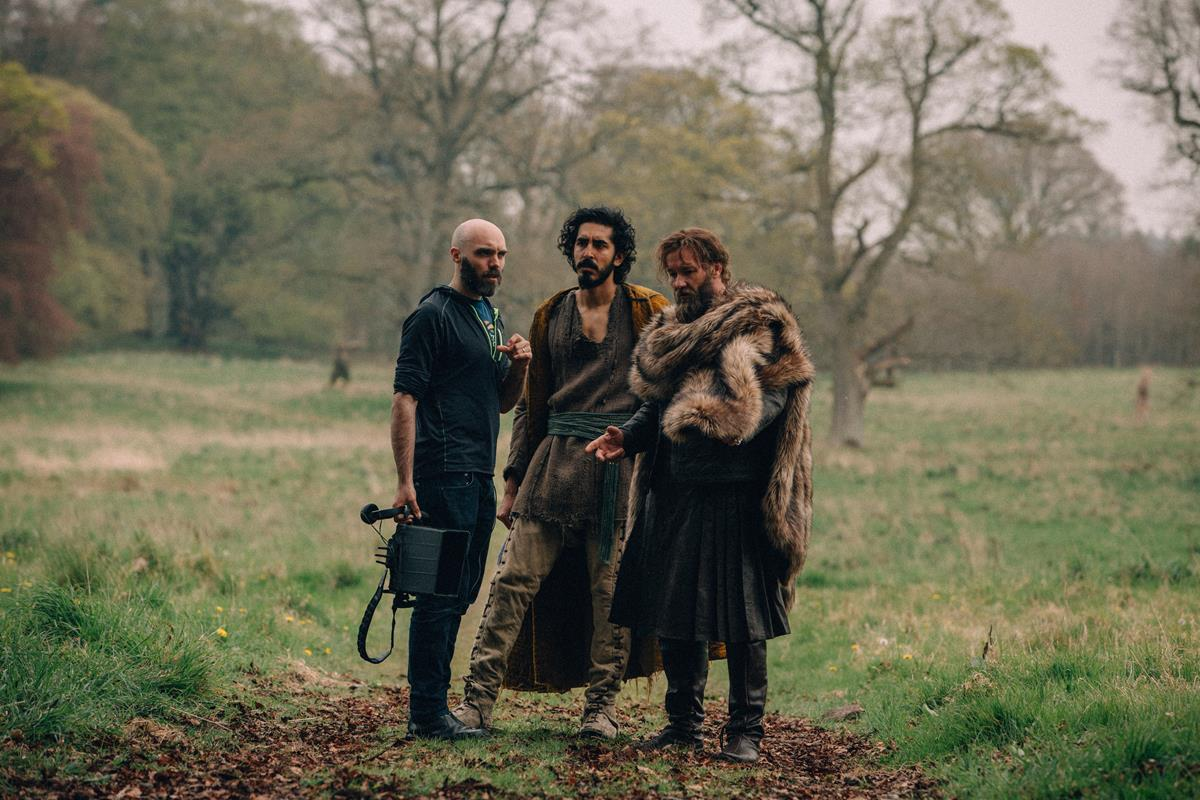 """Director David Lowery, Dev Patel and Joel Edgerton on the set of """"The Green Knight."""" Cr: Eric Zachanowich/A24"""