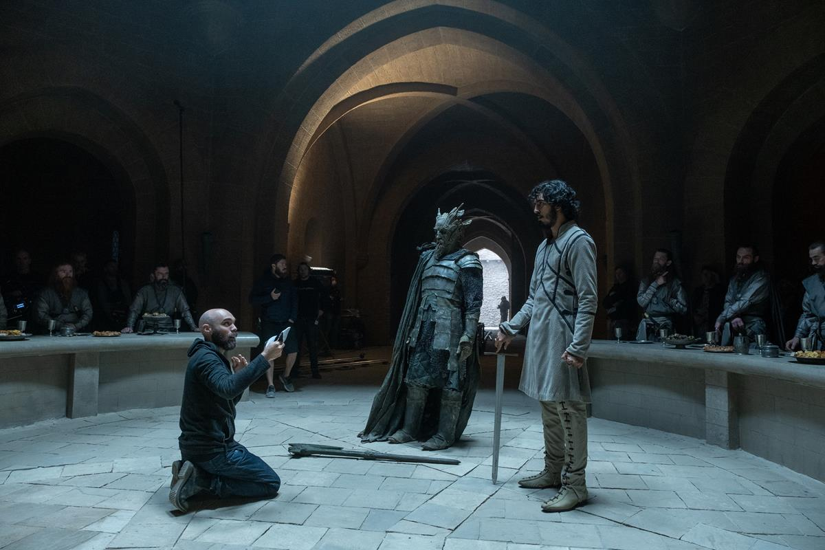 """David Lowery, Ralph Ineson and Dev Patel on the set of """"The Green Knight."""" Cr: Eric Zachanowich/A24"""